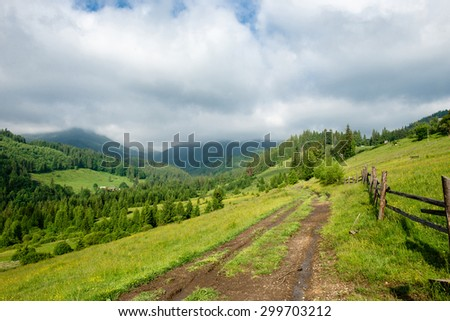 Ground road through beautiful mountain landscape at the sunny day - stock photo