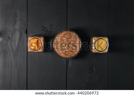Ground spices in bottles with grain flax in glass plate on black wooden background. Top view. - stock photo