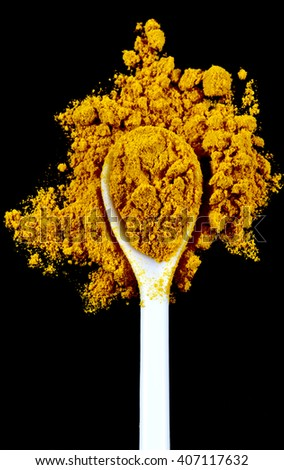 Ground turmeric spice in a white spoon isolated on a black background - stock photo