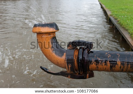 ground water being pumped away into a pond - stock photo