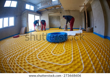 grouo of workera installing underfloor heating and colling in modern home - stock photo