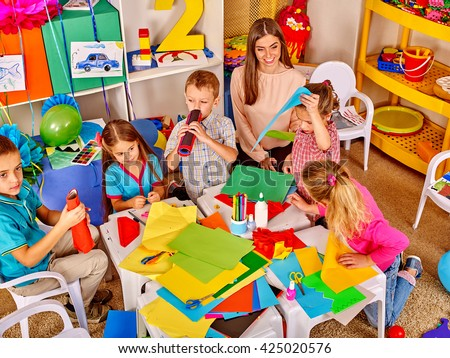 Group children make by hand of colored paper  in kindergarten school . - stock photo