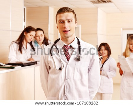 Group doctors standing at reception in hospital. - stock photo