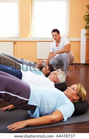 Group doing back exercises in a gym with fitness trainer - stock photo