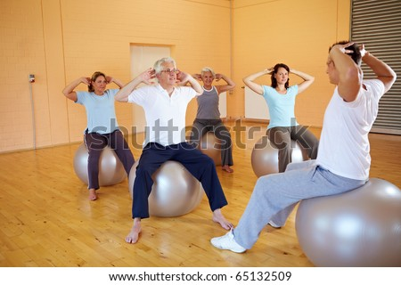 Group doing back exercises with Swiss ball in gym - stock photo