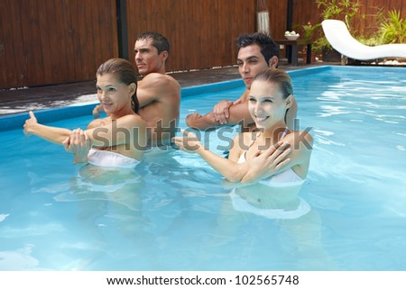 Group doing water aerobics in blue swimming pool