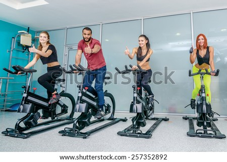 Group fitness exercises in the gym. Five athletes pedaling and looking at the camera on a stationary bike at the gym. Athletes dressed in sports clothes and show a thumbs up - stock photo