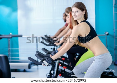 Group fitness training. Athletic girl pedaling and looking at the camera on a stationary bike at the gym while her girlfriend athletes pedaled on bicycles in the background - stock photo