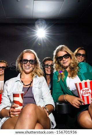 Group friends with snacks watching 3D movie in theater - stock photo