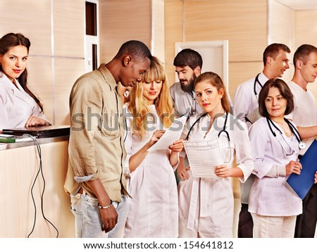 Group happy doctors standing at reception in hospital. - stock photo