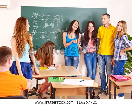 Group happy student in classroom near blackboard.