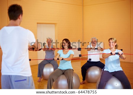 Group in a gym doing fitness exercises with a flexibar - stock photo