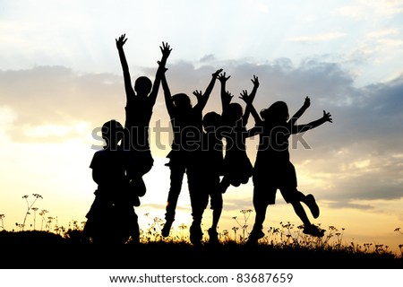 Group jumping children on meadow, sunset, summertime - stock photo