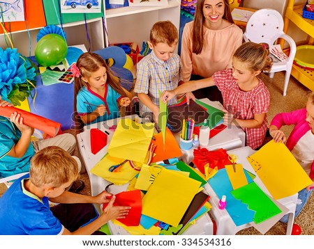 Group kids holding colored paper and glue on table in kindergarten . Top view. - stock photo