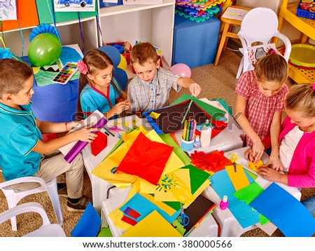 Group kids keeps colored paper on craft lesson in kindergarten . - stock photo