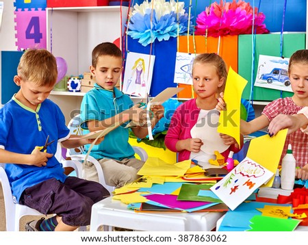 Group kids make applique of colored paper on table in kindergarten . - stock photo