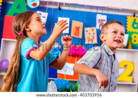 Group kids playing with origami airplane in kindergarten . Girl looking up. The boy is happy. - stock photo