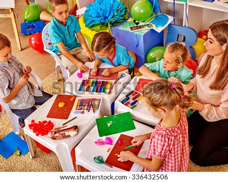 Group little girl and boys holding colored paper and glue on table in kindergarten . - stock photo