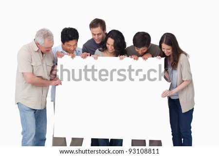 Group looking at blank sign in their hand against a white background - stock photo