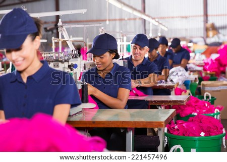 group multiracial factory workers sewing in clothing factory - stock photo