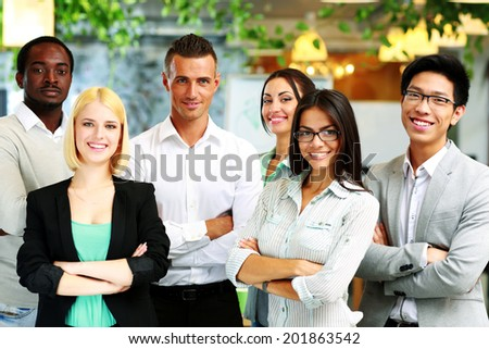 Group of a happy businesspeople standing together in office - stock photo