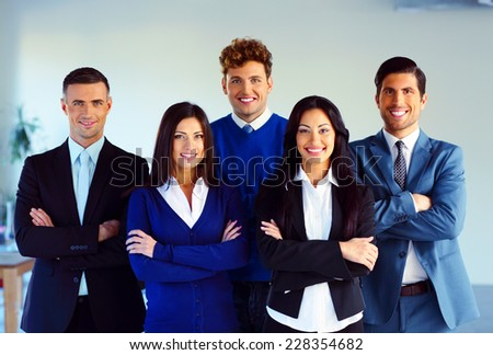 Group of a happy co-workers standing with arms folded in office - stock photo