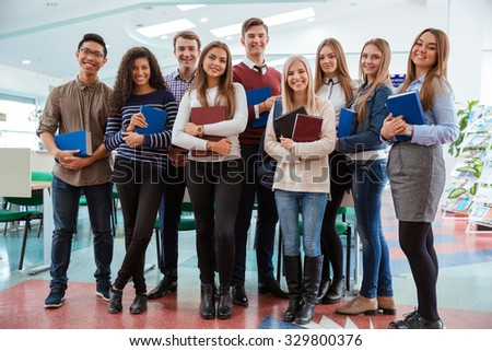 Group of a happy students standing in classroom together and looking at camera - stock photo
