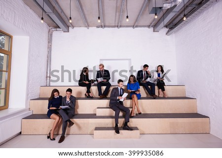 Group of a skilled professionals are working with paper documents on a lecture on logistics in business school. Men and women managers of successful company are developing a concept of a new project - stock photo