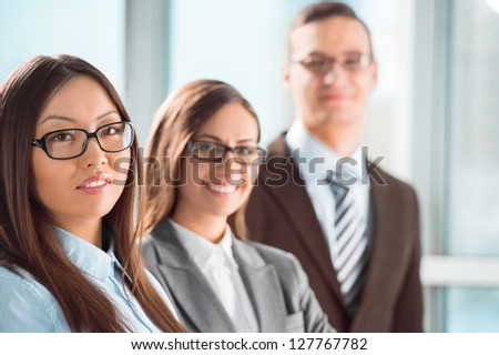 Group of a successful business people standing together at office and smiling - stock photo