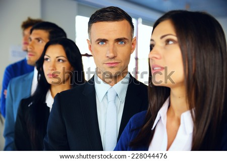 Group of a young serious businesspeople standing in row at office - stock photo