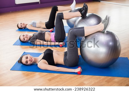 Group of active smiling women are training in fitness club with exercise balls and dumbbells. Smiling and looking at the camera.