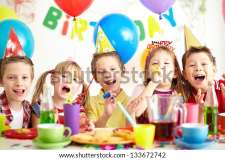 Group of adorable kids having fun by festive table at birthday party - stock photo
