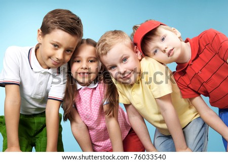 Group of adorable kids looking at camera on blue background - stock photo