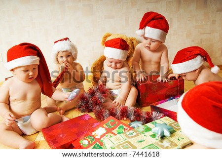Group of adorable toddlers in Christmas hats packing presents