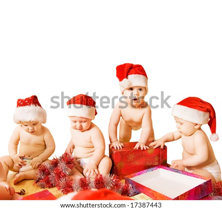 Group of adorable toddlers in Christmas hats packing presents. Isolated on white background - stock photo