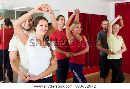Group of adult american people dancing salsa in studio - stock photo