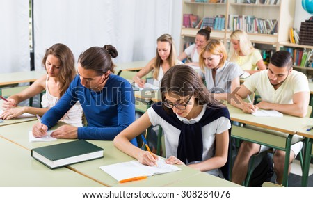 Group of adult pupils studying together in classroom - stock photo