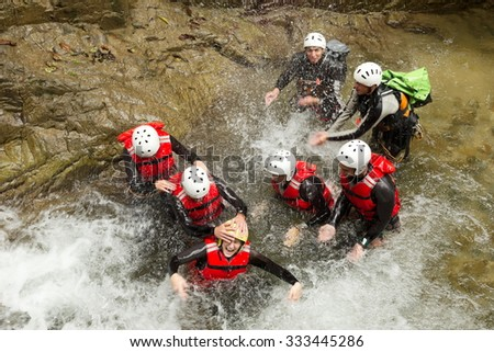 Group Of Adventurous People Fooling Around In A Natural Pool - stock photo