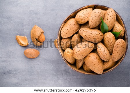 Group of almond nuts with leaves.Wooden background. - stock photo