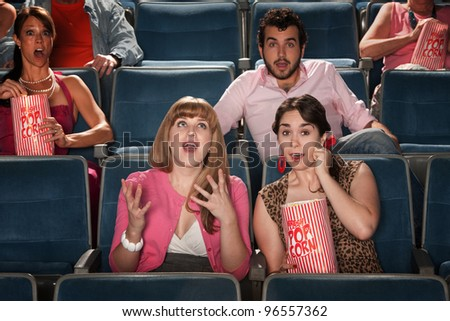 Group of amazed people watch movie in theater