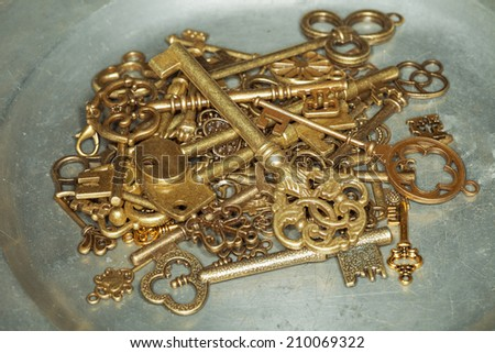 Group of antique golden door keys on iron plate - stock photo