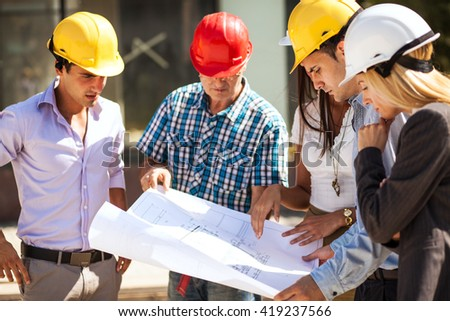 Group of architects and experts discuss about construction.Holding blueprint of new project. - stock photo