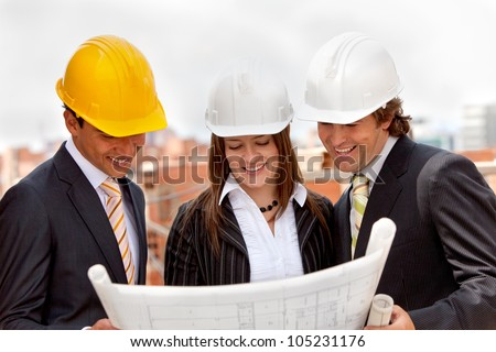 Group of architects at a construction site looking at the blueprints - stock photo
