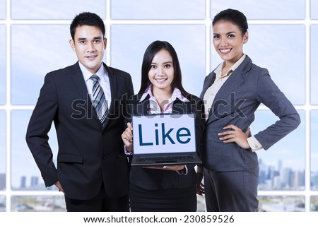 Group of asian business people showing like on laptop at office - stock photo