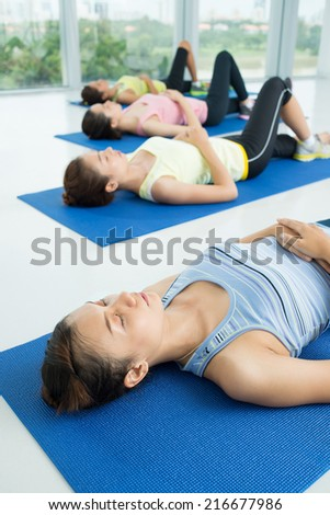Group of Asian sporty women doing relaxing exercise on the floor - stock photo