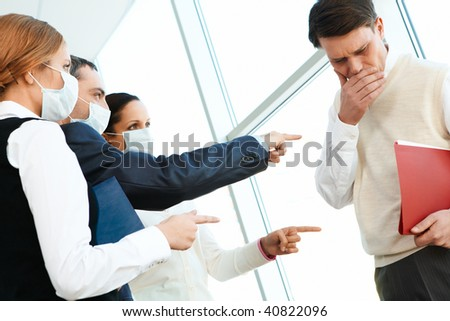 Group of associates in protective masks pointing at coughing man - stock photo