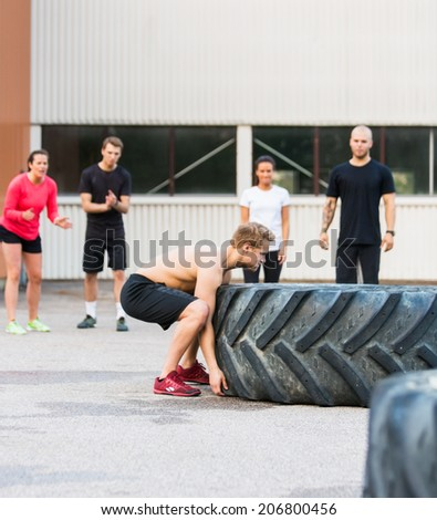 Group of athletes motivating friend in flipping tire outdoors - stock photo