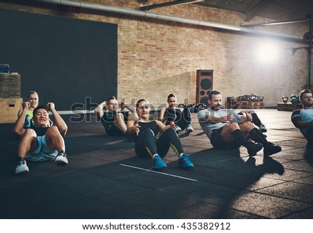 Group of athletic adult men and women performing sit up exercises to strengthen their core abdominal muscles at fitness training - stock photo