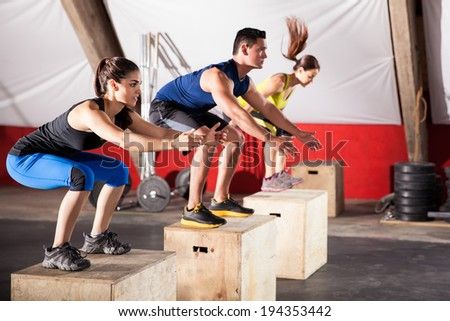 Group of athletic people jumpin over some boxes in a cross-training gym - stock photo