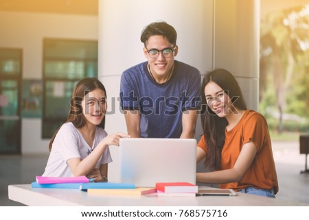 Group of attractive young people using a laptop and tablet, sitting on the floor, Social media online concept.